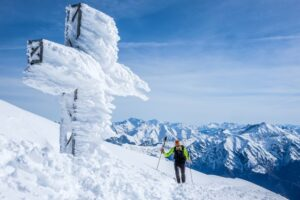 A skier walks past a snow and ice covered cross atop a mountain in front of a mountain range and blue skies