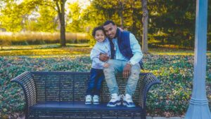 a father and his small son pose on a park bench smiling