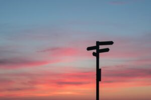 a signpost with serval options silhouetted against a sunrise - pink, blue and orange sky