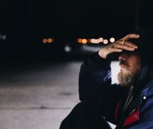 man sits on street at night holding his face in his hand