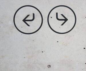 concrete wall with arrows pointing left and right