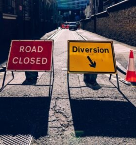street with road closed diversion signs with arrow pointing right