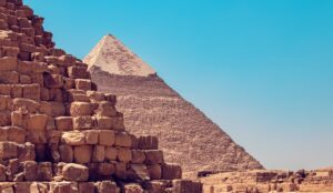 closeup of a pyramid with another pyramid in the background, blue sky