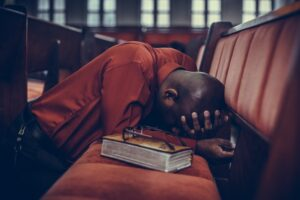a man in a church bent over a pew praying with bible next to him