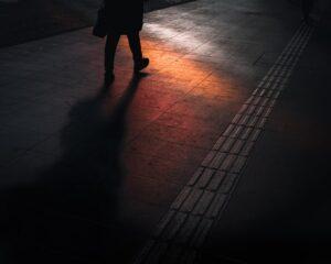 man walking on dark street with orange and red light reflecting off floor