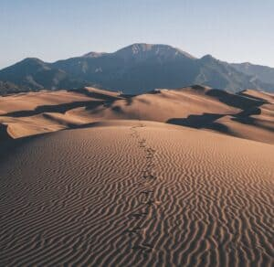 Footprints in the desert leading to mountains