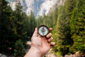 Hand holds compass with a view of forest and mountains