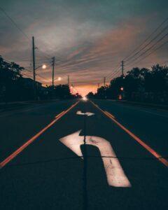 Arrow turning left on a dark tarmac road