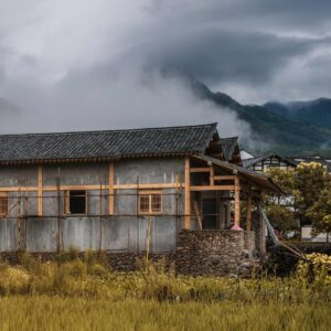 an almost-constructed traditional rural chinese house with misty hills in the background