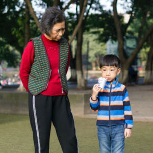 an older lady and a young boy stand together in a park