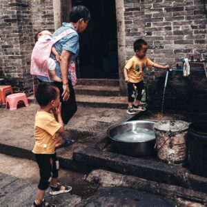 a parents supervises two young boys fetching water from an outdoor tap