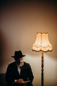 man in hat reads book by a lamp